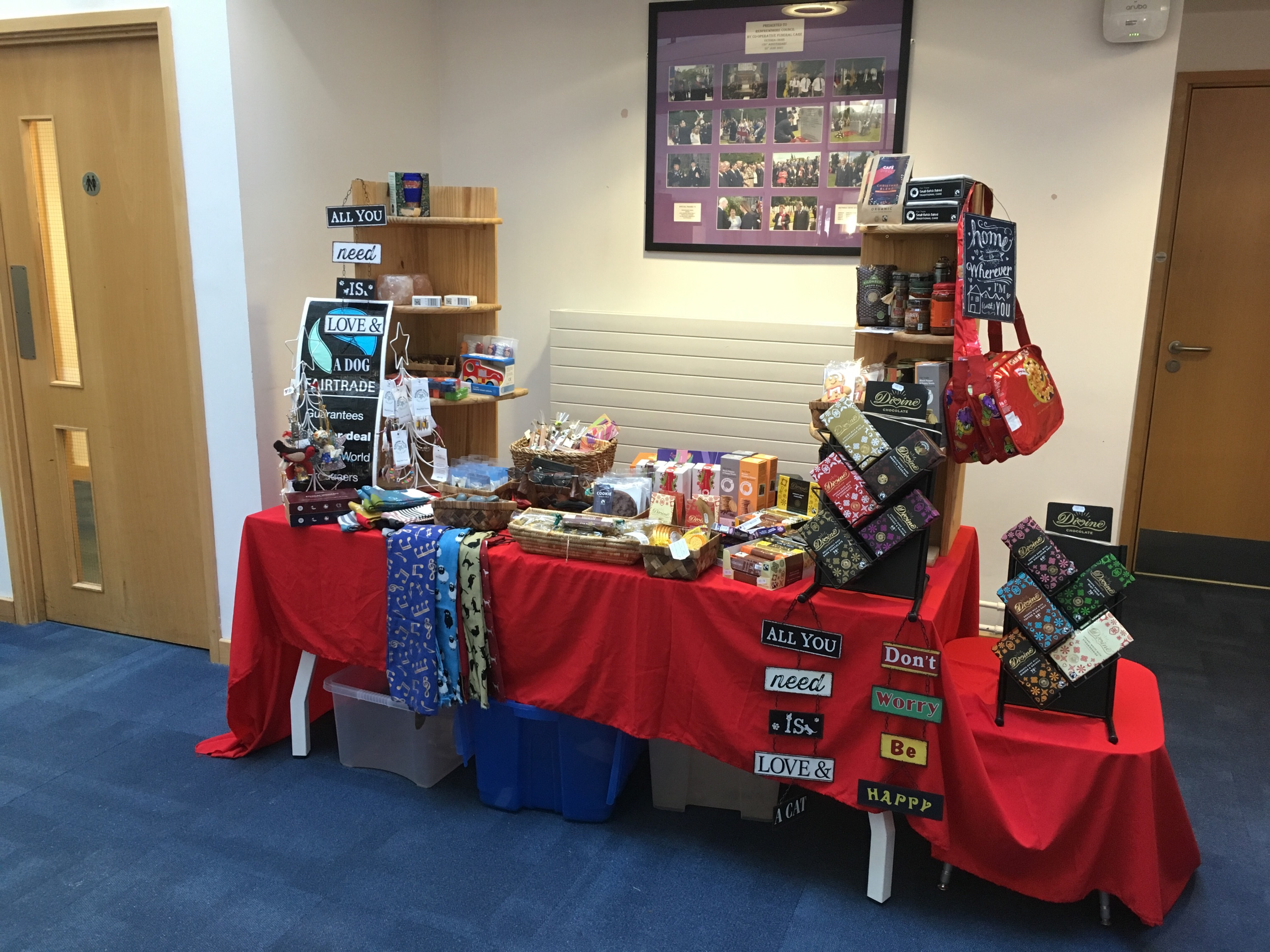 Stall displaying fair trade items including chocolate, scarves, biscuits and wall hangings