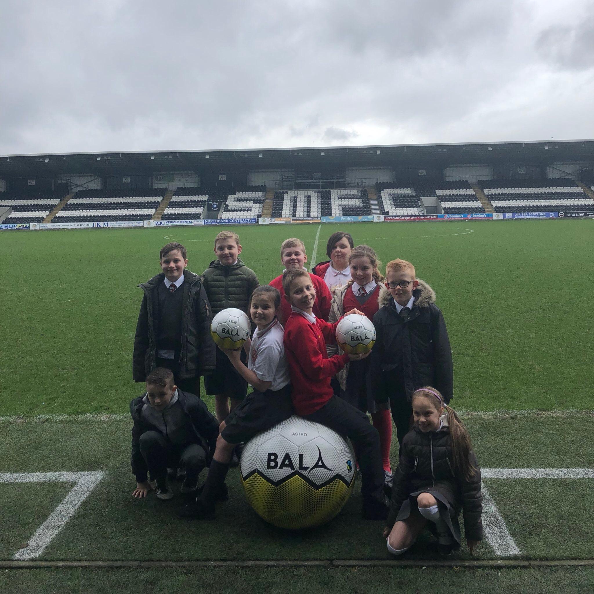 10 children pose in football grounds, two holding a fair trade ball each and sitting on top of a giant ball